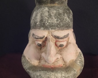 frowning face of a Dwarf in clay pottery
