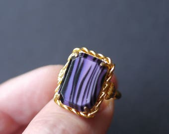 Gold tone ring with purple glass black striped stone