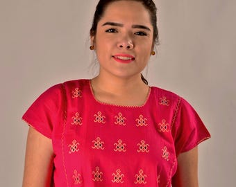 Pink blouse with turtle decorations.