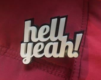 Badge: Silver and black 'Hell yeah!' brooch in cast acrylic