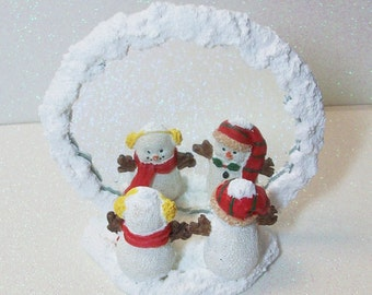 Pair of Snowmen checking their new hats in a snow covered mirror ornament or figurine