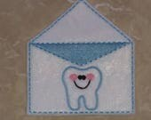 White tooth fairy envelope with blue stitching.