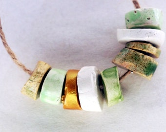 It is enough -- a set of 9 green, white and gold small ceramic beads