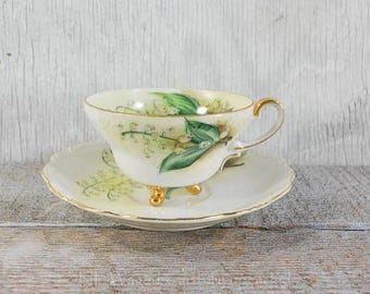 Vintage footed teacup with matching saucer, handpainted,  gold detailing, lily of the valley