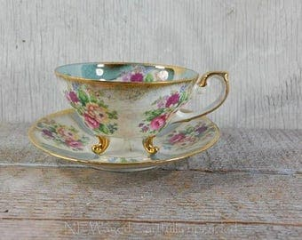 Vintage footed teacup with matching saucer, pearlescent,  gold detailing, floral pattern
