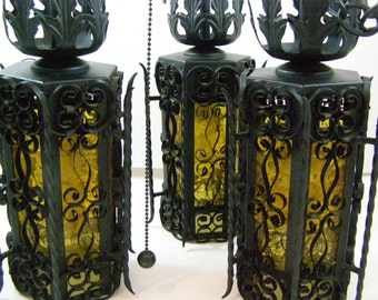 Mediterranean Style 3 Light Pendant Black Scrolled Wrought Iron Ceiling Fixture with 6 Amber Textured Glass Panels. Made in Mexico 1960's.