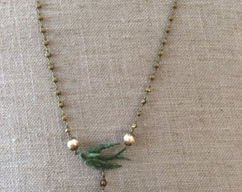 Antiqued brass necklace with verdigris bird