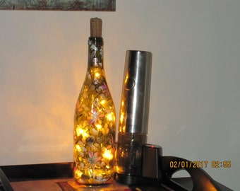 Brown Wine bottle with pink and white daisies green leaves also white baby breath thoughouth the bottle lights inside