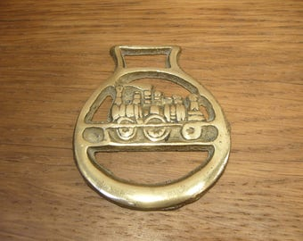 Vintage horse brass with a steam locomotive on two rails in a plain surround