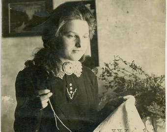 Pretty woman embroidering antique photo