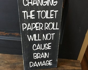 Changing the toilet paper roll does not cause brain damage, bathroom sign
