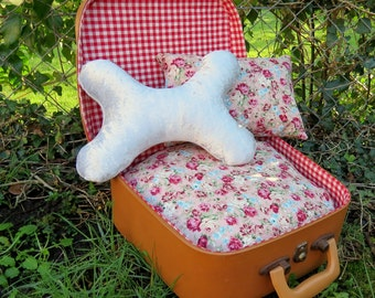 A quirky bed for a handbag dog or small cat.  Made from a 1960s vanity case.
