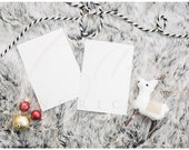 Double blank holiday christmas card mockup stock photo on gray fur with red ornaments, black and white striped rope ribbon, cute reindeer