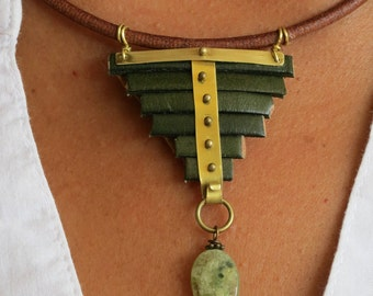 Pyramid shaped leather necklace with green grenat oval and flat stone. Bronze clasp.