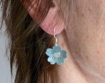 Pair of anodized titanium, silver earrings. Cool ice blue anodized titanium, silver pair of swinging blossom earrings.