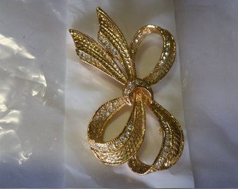 golden bow brooch with inlaid crystals