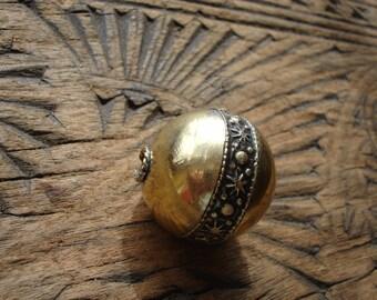 Moroccan  shiny  medium gold colour ornate round slightly dented bead