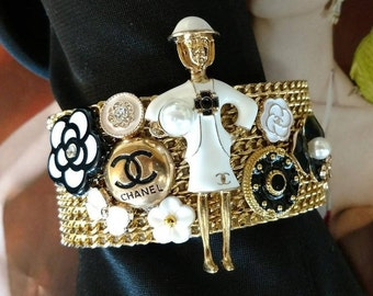 Iconic One-of-a-Kind Bracelet Authentic and Inspired embellishments. Gold chain leather cuff bracelet. Brooch Buttons Flowers Lady Coco