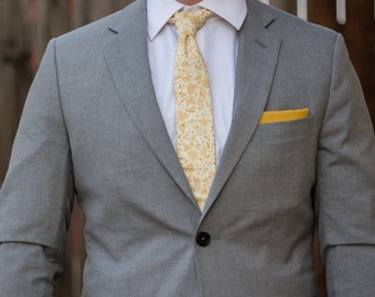 Off-white skinny tie with dark yellow/mustard floral pattern