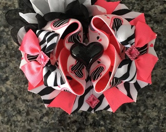 Hot pink and zebra print boutique hair bow with a french barrette attached to the back.