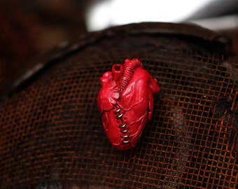 Pendant is an anatomical heart, sewed with iron rivets.