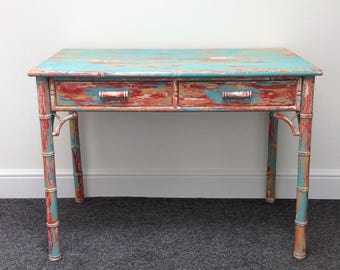 Distressed, shabby chic vintage table in red, blue and gold