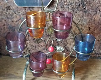 Atomic glasses coloured shot glasses on stand. Vintage bar