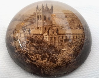 Vintage glass paperweight depicting Buckfast Abbey in Devon. 1900s antique domed souvenir picture paperweight. .