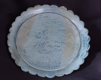 Green glazed ceramic plate with subtle pattern