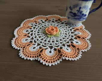 Crochet doily- white with orange/peach center flower and border