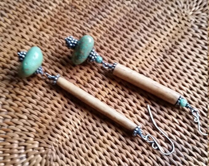 These Asymmetrical Earrings are made of Bone, Sterling Silver, And Turquoise