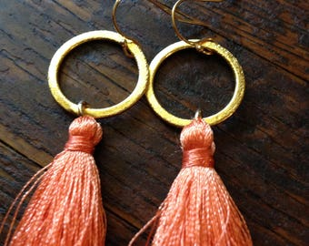 Orange silk tassel earrings on brushed gold hoops.