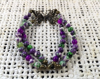 Purple and green double stranded butterfly bracelet