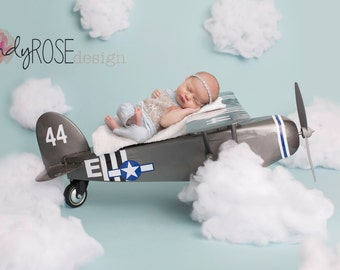Newborn airplane in the clouds backdrop