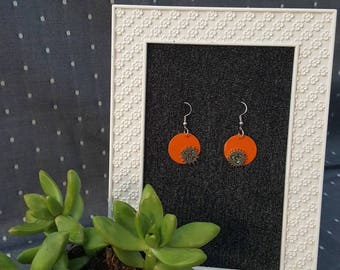 Orange circle earrings with gears, blue accent under gears