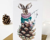 Rabbit sat on a glittered pinecone Christmas card. Featuring miniature toadstools. Iridescent glitter. Card for rabbit lovers.