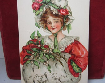 Colorful 1910 gold gilded Ernest Nister, E. P. Dutton christmas postcard pretty edwardian girl in christmas outfit,muff w/ mistletoe