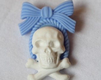 """Skull & Bow"" white and blue pin"
