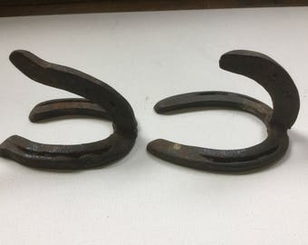 Primitive early black cast iron horse shoe hooks  Western decor