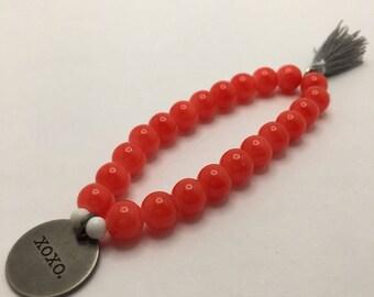 Orange beaded flexible bracelet with a Round Antiqued Silver XOXO charm & Gray Tassel.