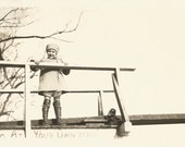"Vintage Snapshot ""Diving At Your Own Risk"" Cute Little Girl Wooden Bridge Sign Leather Boots Winter Coat Hat Found Vernacular Photo"