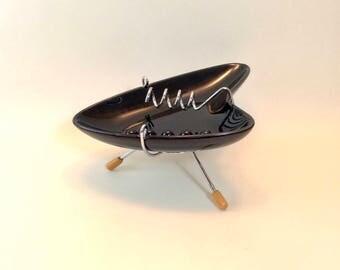 Retro black ceramic boomerang or shark fin ashtray on chromed tripod. Atomic era style ashtray.