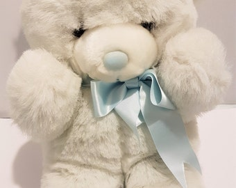 Vintage teddy bear, cute white bear with a pretty blue bow ribbon, traditional child's fluffy cuddly bear from the 1980s