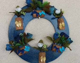Wreath in blue, decorated with corks, flowers and bows.