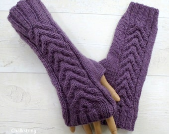 Hand knitted longer length plum wristwarmers with cables. Fingerless gloves