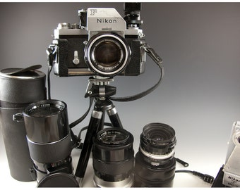 Silver n Black Vintage Nikon F 35 mm Camera with three additional lenses , fiilters , flash, tri pod, carry case and more, very nice set up