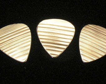 3 bronze guitar picks made from damaged cymbals