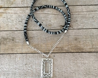 Necklace long motives ethnic, black and white, with feathers.