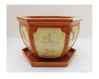 A handmade stoneware planter / plant pot with high relief decoration of two flying storks