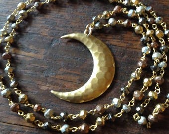 Hammered brass moon on a mixed pyrite rosary chain.